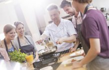 Students watching chef teacher in cooking class kitchen — Stock Photo