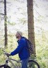 Hombre con mochila y montaña bicicleta en el bosque soleado - foto de stock