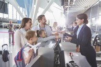 Customer service representative checking family tickets at airport check-in counter — Stock Photo