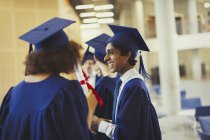 Smiling college graduates in cap and gown — Stock Photo