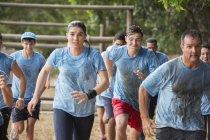 Team läuft im Regen auf Bootcamp-Hindernisparcours — Stockfoto