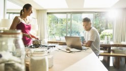 Couple cooking and working at laptop in morning kitchen — Stock Photo