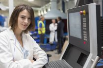 Portrait smiling female engineer at control panel in steel factory — Stock Photo