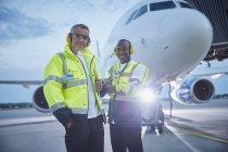 Портрет уверенных работников наземного управления воздушным движением возле самолета на взлетной полосе аэропорта — стоковое фото