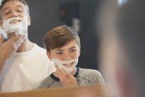 Pai assistindo filho fingindo barbear rosto no espelho do banheiro — Fotografia de Stock