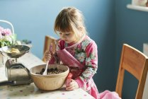 Curious girl baking with mixing bowl in kitchen — Stock Photo