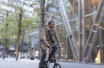 Uomo d'affari aziendale in bicicletta fuori edificio moderno — Foto stock