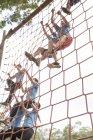 Люди лазают по сетям на полосе препятствий в учебном лагере — стоковое фото