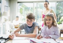 Portrait smiling brother and sister doing homework — Stock Photo
