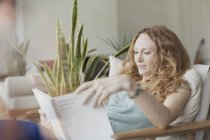 Woman reading book in armchair — Stock Photo