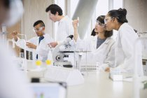 Étudiants menant une expérience scientifique dans une salle de classe de laboratoire scientifique — Photo de stock
