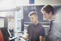Trabalhadores, revendo a papelada no painel de controle de máquinas na fábrica de aço — Fotografia de Stock