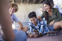 Teenage friends hanging out texting with cell phone at skate park — Stock Photo