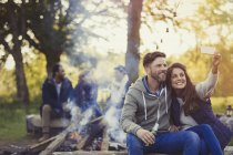 Smiling couple taking selfie with camera phone near campfire — Stock Photo