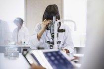 Étudiante utilisant un microscope dans une salle de classe de laboratoire scientifique — Photo de stock