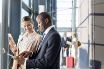 Business people using digital tablet in airport — Stock Photo