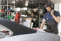 Mechanic talking on cell phone ordering car parts from catalog in auto repair shop — Stockfoto