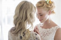 Matron of honor and bride talking in domestic room — Stock Photo