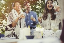 Friends laughing and drinking champagne at birthday party — Stockfoto