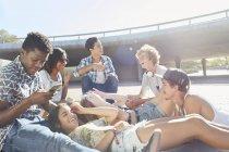 Amis adolescents traînant au skate park ensoleillé — Photo de stock
