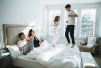 Parents watching children jumping on bed — Stock Photo
