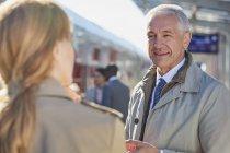Businessman talking to businesswoman on train station platform — Stock Photo