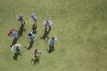 Pessoas girando em aros de plástico na grama ensolarada — Fotografia de Stock