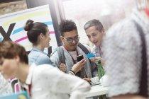 Les gens d'affaires utilisant le téléphone intelligent lors de la conférence technologique — Photo de stock