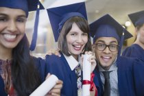Portrait enthusiastic college graduates in cap and gown posing with diploma — Stock Photo