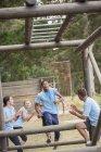 Teammates cheering for man nearing monkey bars on boot camp race course — Stock Photo
