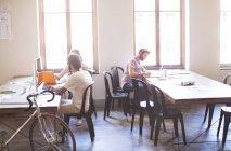 Gente di affari creativa lavorando alle tabelle in ufficio soleggiata — Foto stock