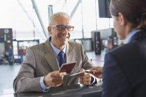 Улыбающийся бизнесмен, выдающий паспорт представителю службы поддержки клиентов на стойке регистрации в аэропорту — стоковое фото