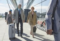 Business people walking pulling suitcases outside airport — Stock Photo