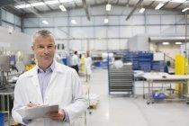 Porträt lächelnder Ingenieur mit Klemmbrett in Stahlfabrik — Stockfoto