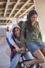 Chicas adolescentes juguetonas montando bicicleta BMX en el parque de skate - foto de stock