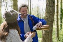 Пара Піші прогулянки і пити каву з ізольованих напій контейнера в лісі — стокове фото