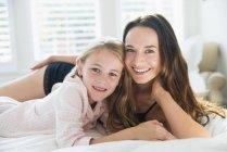 Портрет улыбающейся матери и дочери, лежащих на кровати — стоковое фото