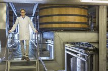 Portrait confident vintner in lab coat on platform in winery cellar — Stock Photo