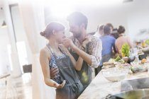 Playful couple enjoying cooking class in kitchen — Stock Photo