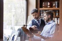 Geschäftsleute, die Prüfung Kleidschuhe im Herrenmode shop — Stockfoto
