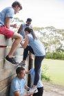 Compagni di squadra che aiutano la donna oltre il muro sul campo di addestramento percorso ad ostacoli — Foto stock