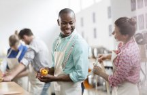 Smiling woman tying apron for man in cooking class kitchen — Stock Photo