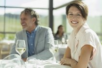Portrait smiling woman drinking wine in sunny restaurant — Stock Photo