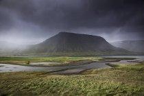 Cerro contra el agua del estanque y tiempo nublado - foto de stock