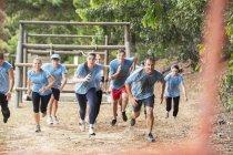 Команда бежит по полосе препятствий учебного лагеря — стоковое фото