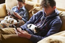 Boys using digital tablet and cell phone with puppies sleeping in laps — Stock Photo