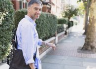 Portrait confident businessman walking and looking back on sidewalk — Stock Photo