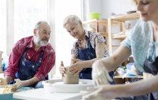 Senior couple using pottery wheel in studio — Stock Photo