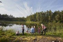 Бабусь і дідусів і онуків риболовля на сонячному березі озера в лісі — стокове фото