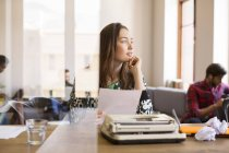 Pensive creative businesswoman with paperwork at typewriter in office — Stock Photo